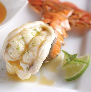 Lobster tail with drizzled butter and a side of lime wedges
