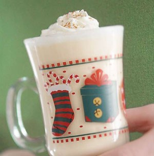 Decorated glass Christmas mug filled with orange nog and topped with whipped cream