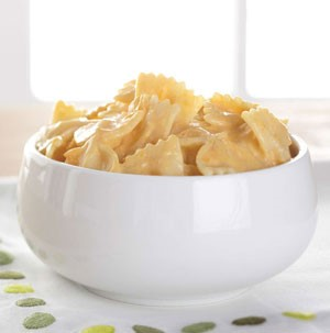 Cheese sauced bow tie pasta in a tall white bowl