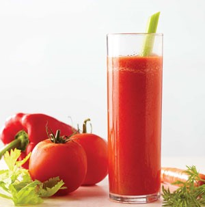 Tall glass filled with red juice and garnished with celery stalk next to fresh carrots, tomatoes, and red bell pepper