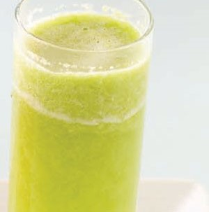 Tall glass filled with green apple and kiwi popper drink