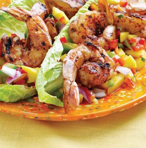 Tail on shrimp on top of salsa made with various fruits and romaine lettuce
