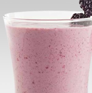 Glass filled with pink smoothie and garnished with blackberries