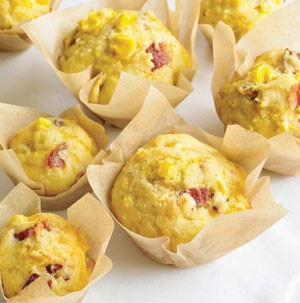 Yellow corn muffins stuffed with bacon and cheese in parchment cups
