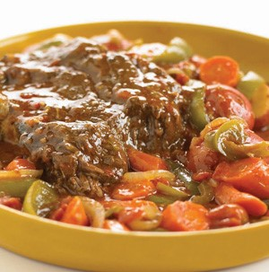 Pot roast with sliced squash, carrots, peppers and onions in a yellow bowl