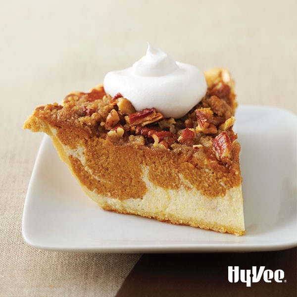 Pumpkin pie swirled with cream cheese and chopped pecans and whipped cream on top