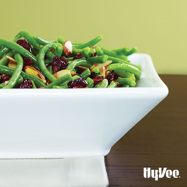 Green beans, sliced almonds, and dried cranberries in white serving dish