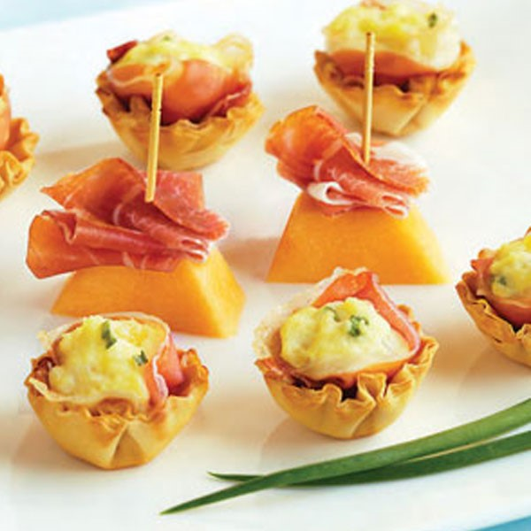 Prosciutto-cheese bites next to cantaloupe and prosciutto on toothpicks
