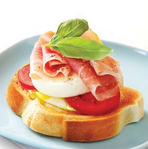 Slice of french bread topped with tomato, mozzarella, prosciutto, egg and basil