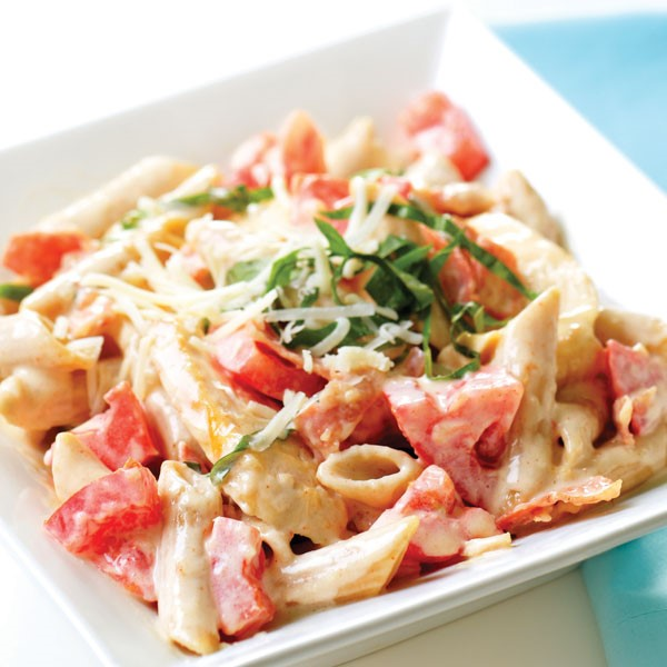 Bowl of penne pasta topped with grated asiago cheese and chopped basil