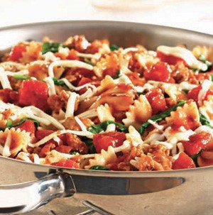 Skillet filled with bow tie pasta, tomatoes, and spinach
