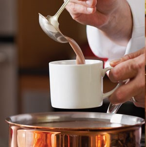Pouring hot cocoa into white mug over copper saucepan