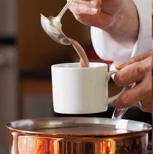 Pouring hot cocoa into white mug over copper saucepan