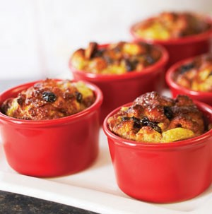 Small red ceramic bowls filled with baked bread pudding