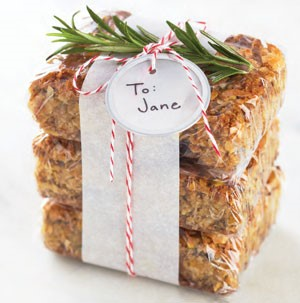 Chewy Oatmeal-Cherry Bars stacked and wrapped together with string and sprig of Rosemary