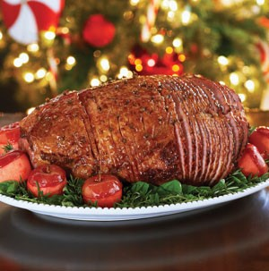 Glazed and sliced holiday ham on a bed of mixed greens
