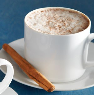 Foamed latte topped with ground cinnamon in a white mug and cinnamon stick on the side