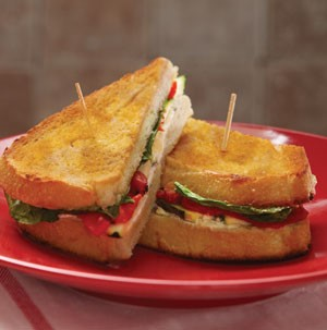 Toasted sandwiches filled with red pepper, sliced meat. and lettuce leaves on a red plate