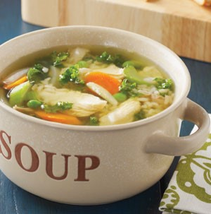 Chicken soup with peas, chopped celery and carrots, and grains in white serving dish