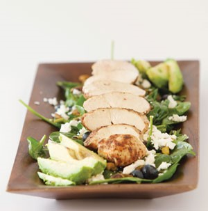 Plate of spinach topped with chicken, blueberries, avocado, feta and pistachios