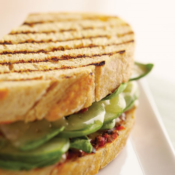 Grilled panini filled with olive tapenade, sliced cheese, spinach and cucumber slices