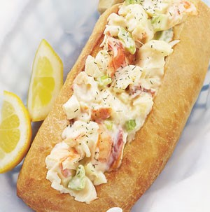 Rolls filled with lobster meat and a creamy sauce with two lemon wedges on the side