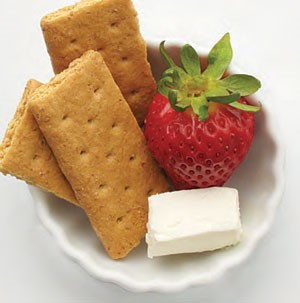 Bowl of graham crackers, cube of cream cheese and a fresh strawberry