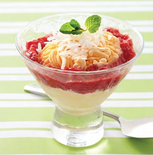 Cup filled with vanilla ice cream and smashed strawberries, and topped with shredded coconut and a mint leaf