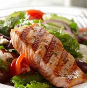 Salad filled with mixed greens, chopped tomatoes, crumbled cheese, sliced red onion, and grilled salmon fillet