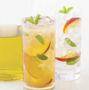 Glass of iced tea, garnished with peach slices and mint leaves
