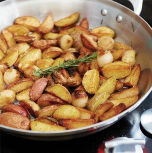 Skillet filled with roasted potato wedges and garnished with fresh rosemary sprig