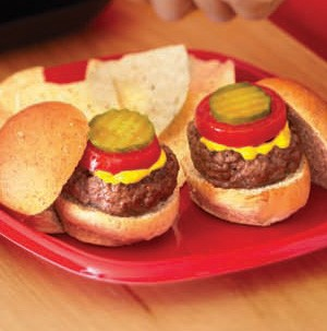 Mini hamburger buns topped with burger patty, yellow mustard, red tomato slice, and pickle slice on a red plate with tortilla chips on the side