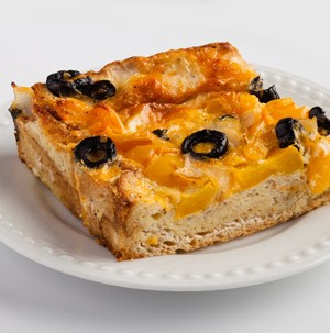 Crust topped with cheese and sliced black olives on a white plate