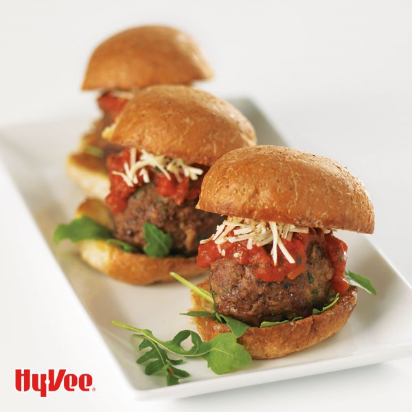 Bun topped with arugula, meatball, red sauce, and shredded cheese