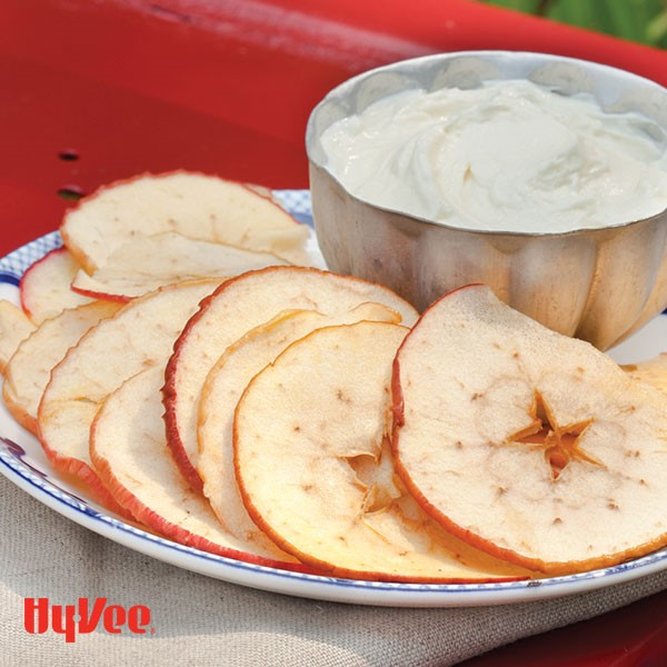 Thinly sliced apple chips on a plate next to bowl filled with white goat cheese dip