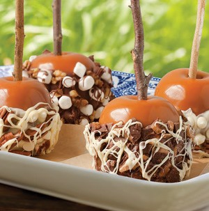 Plate of Caramel Apples on a Stick covered in Milk and White Chocolate, Marshmallows, Heath bar, Walnuts and Pecans