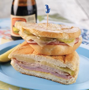 Two Cuban Sandwich halves stacked on a blue plate with a toothpick and pickle