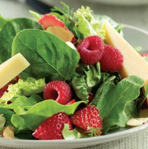 Plate topped with mixed greens, cheese wedges, sliced strawberries, and whole raspberries