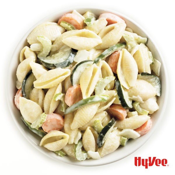 Pasta salad mixed with cucumber, onion, carrots, radishes and green bell pepper