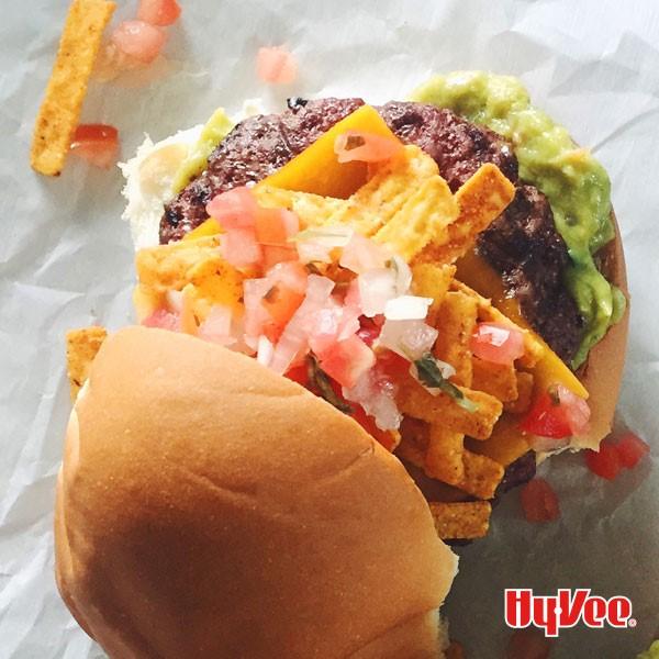 Bun topped with guacamole, burger patty, cheese, corn chips, and pico de gallo.
