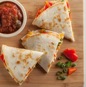 Quesadilla wedges on a wooden cutting board with a side of chopped tomatoes, green onions and a bowl of salsa
