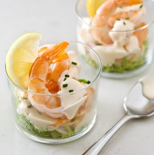 Spicy warm shrimp cocktail served in glass cup with spoon