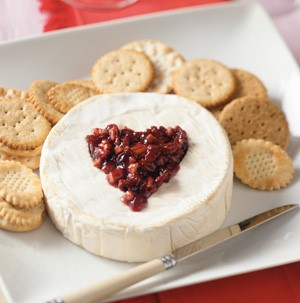 Plate of brie topped with fruit preserve mixture, and served with crackers and a cheese knife