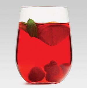 Glass of sparkling red wine sangria filled with fresh raspberries and garnished with an orange slice and mint leaf