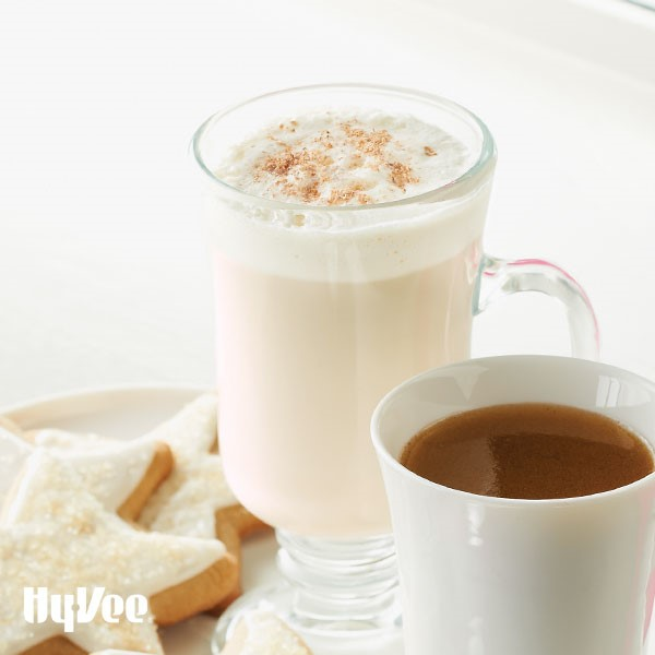 Glass mug of Eggnog, dusted with Nutmeg next to plate of sugar cookies and mug of coffee