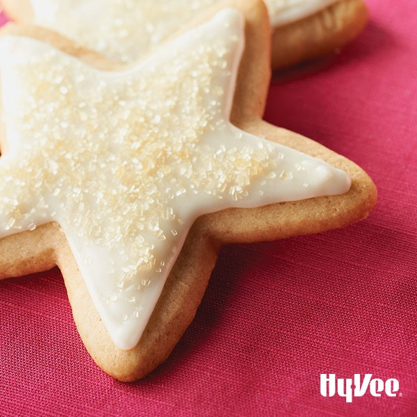 Spice cookies topped with white icing and clear sprinkles