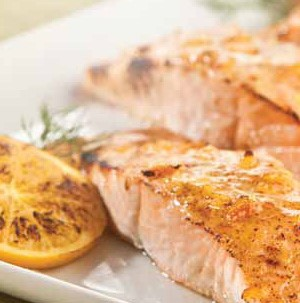 Plate of salmon fillets topped in an orange citrus sauce