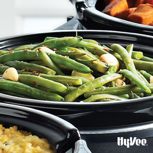Fresh green beans and garlic cloves on a black plate garnished with red pepper flakes