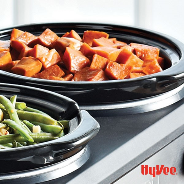 A slow-cooker filled with fresh green beans and a slow-cooker filled with sweet potato chunks