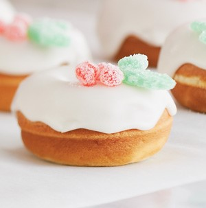 Donuts topped with white icing and garnished with red and green spice drop candies